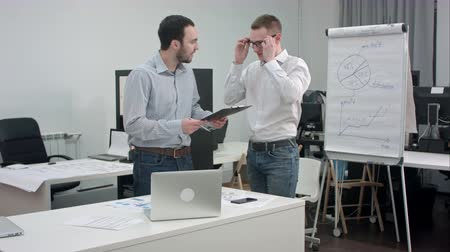 elszánt : Two corporate executives having business discussion in office