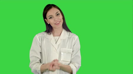 one by one : Smiling young woman in lab coat talking to the camera on a Green Screen, Chroma Key Stock Footage