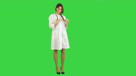 barátságos : Young beautiful nurse posing with stethoscope on a Green Screen, Chroma Key