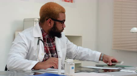 csodálkozó : Afroamerican physician filling in medical forms and answering phone calls at his desk Stock mozgókép