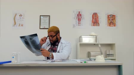 x ray image : Afroamerican doctor analyzing xray and making notes in medical office