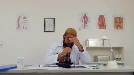 deprivation : Afroamerican male physician tired after long working day