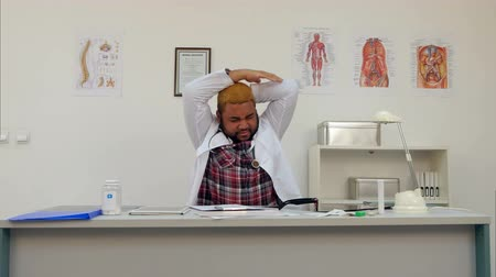 deprivation : Tired male doctor stretching and exercising after long working day at his desk