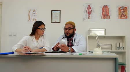 farmacologia : Afroamerican male doctor holding jar of pills while female trainee making notes Stock Footage