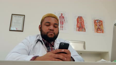 forefinger : Afroamerican male doctor using mobile phone