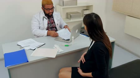 persons : Young pregnant woman visiting physician and giving him some medical papers