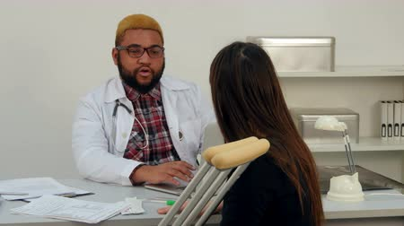 kule : Young woman with crutches having appointment with Afroamerican male doctor Wideo