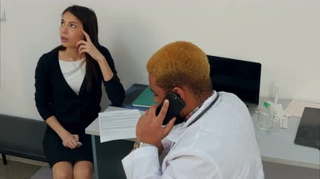 criticize : Afroamerican male doctor talking on the phone making his female patient wait