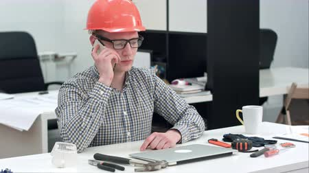 концентрированный : Young architect in helmet having important phone call