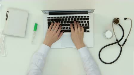 medical thermometer : Female doctor hands typing on laptop keyboard