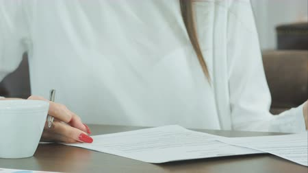 correspondência : Woman hand with red nails signing formal papers