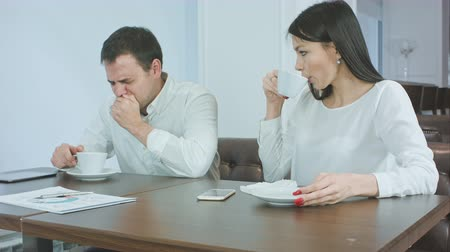 doente : Sick businessman sneezing while anxious female checking his head for fever and giving him napkin Stock Footage