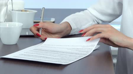 evidência : Woman hand with red nails signing contract