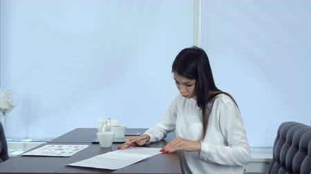 договориться : Young woman signing formal documents sitting at the cafe table