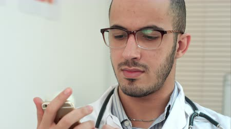 forefinger : Male doctor texting on a smartphone