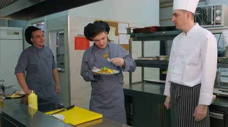 стартер : Young male cooks trying shrimp salad cooked by chef