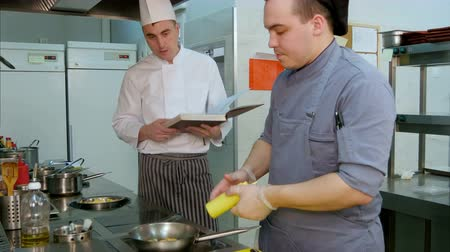 internar : Chef with cookbook instructing cook trainee how to fry shrimps Stock Footage