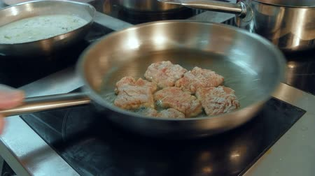 being cut up : Meat being fried in a frying pan on the stove
