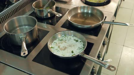 being cut up : Dishes in frying pans being cooked on a stove while chef regulating temperature Stock Footage