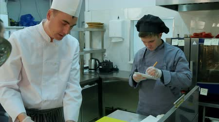 beyazlar : Young trainee watching how chef is cooking and taking notes