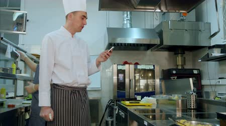 calling telephone : Chef reading something from his phone and talking to one of the cook trainees