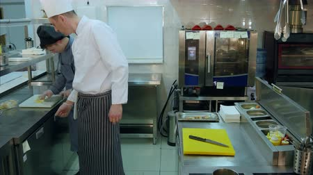 fructose : Head chef watching how young trainee cutting lemon Stock Footage