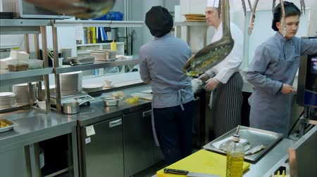 cooktop : Chef cleaning up his workplace while his trainees busy with their kitchen tasks Stock Footage
