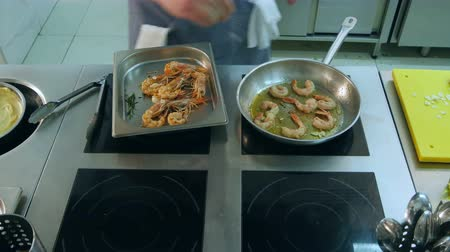 tempura : Chef adding salt and garlic to shrimps frying in a pan