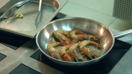 tempura : Chefs male hands putting prawns on a frying pan