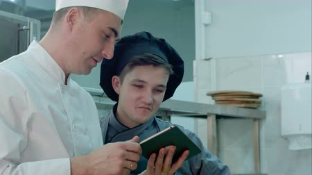 culinária : Chief chef showing cook trainee in hat something funny on digital tablet