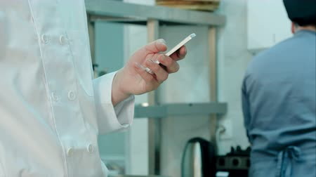 sms : Male chefs hands holding mobile phone in the restaurant kitchen