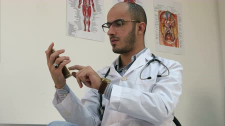 forefinger : Serious male doctor texting on a smartphone