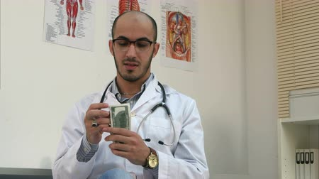 internar : Satisfied male doctor counting money and putting it in his pocket Stock Footage