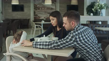 cruelty : Ordinary family of three with little daughter in cafe. Father and mother reassuring their child. Stock Footage
