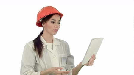 reporting : Female construction specialist in hardhat having a video call via tablet on white background