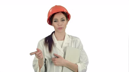 inspection : Female architect in hardhat holding tablet talking to camera on white background Stock Footage