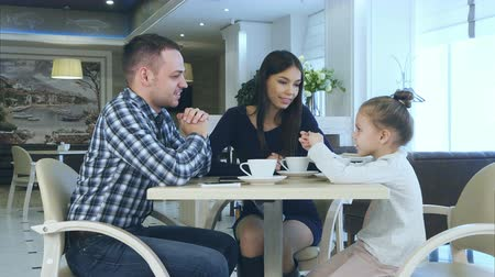 osm : Happy young parents chatting witn daughter during their family vacation in cafe drinking tea. Dostupné videozáznamy