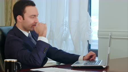 custo : Young businessman stretching his arms in office and start working on laptop Stock Footage