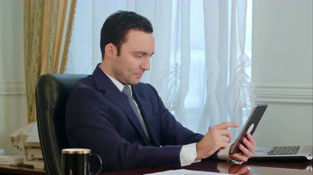 hajózik : Young businessman using modern digital tablet searching the Internet