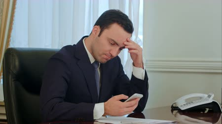 bad looking : Worried businessman looking on smartphone and reading bad news