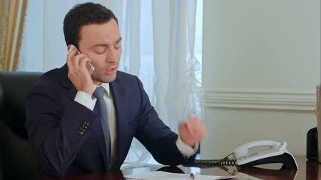 öltözet : Young serious businessman take a phone call, having a conversation and getting pensive