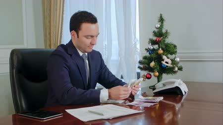 caixa : Happy young businessman counts salary near New Year tree in office