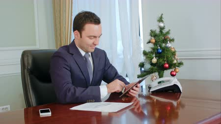 bankier : Young cheerful businessman using modern digital tablet in office Wideo
