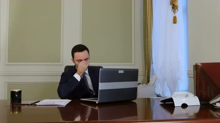 dokončovací práce : Tired businessman finishes working on laptop, relaxing and stretching arms in office