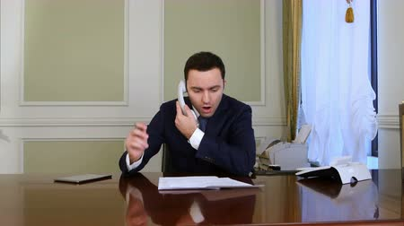 босс : Businessman having trouble while phoning and puts the phone down Стоковые видеозаписи