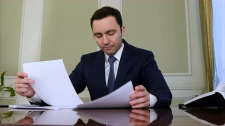перегружены : Portrait of young businessman working on his paperwork in the office