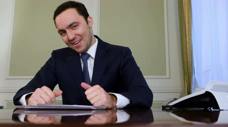 schválení : Smiling businessman with thumb up and showing okey