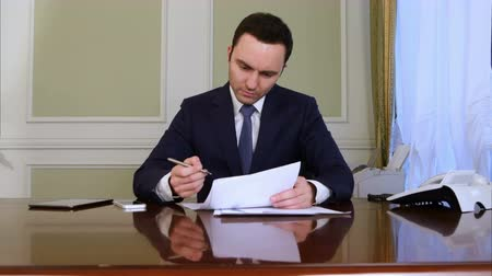 financiamento : Pensive businessman sign documents turning over the sheets