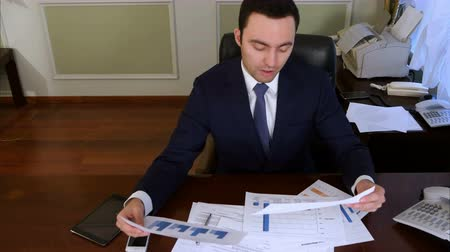 каландр : Confident businessman analyzing investment charts and statistics looking at camera