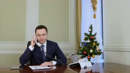 vezérigazgató : Smiling businessman picking up the phone and congratulates business colleagues with Christmas Stock mozgókép
